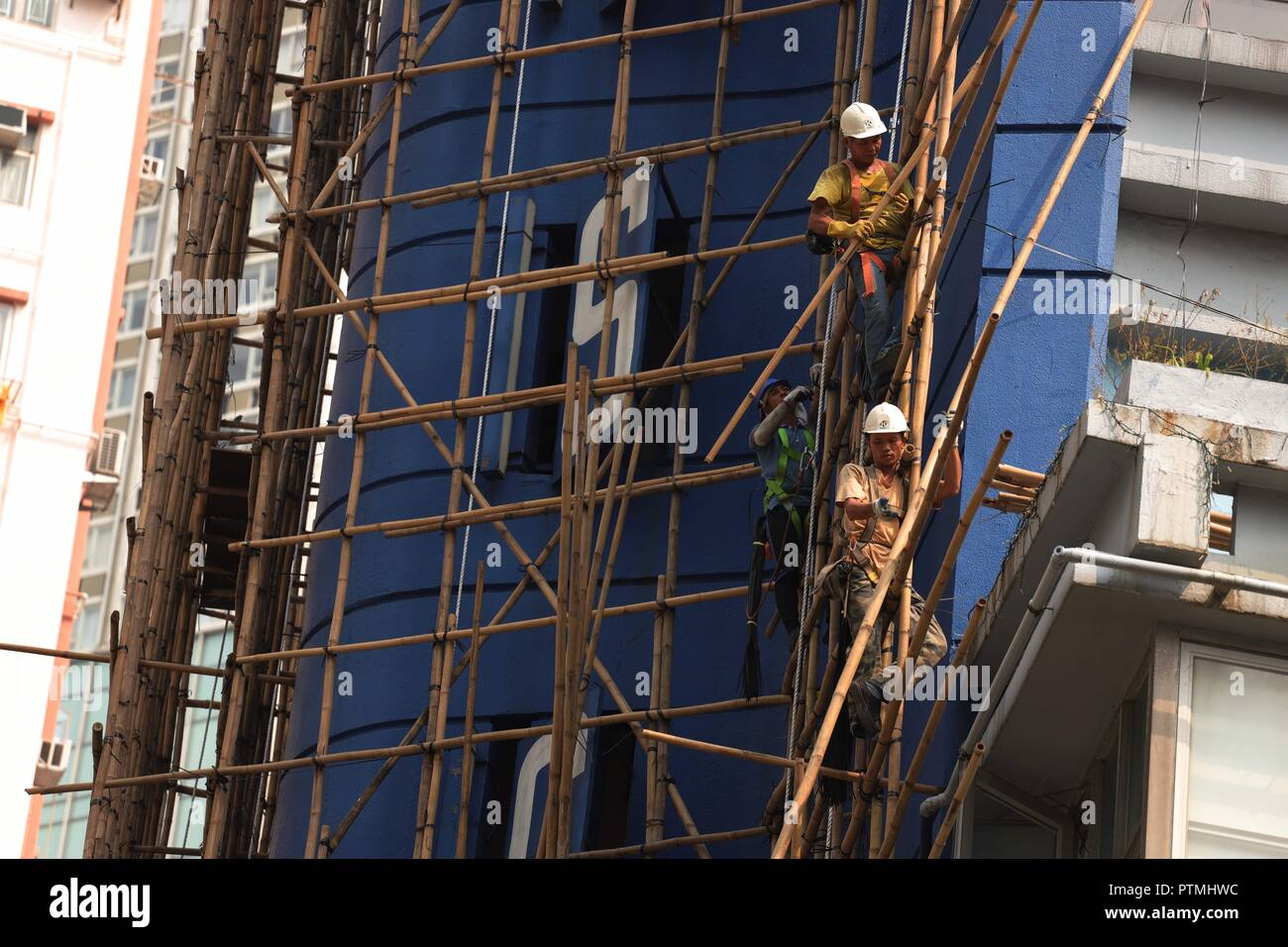 Hong Kong, CHINA. 10th Oct, 2018. Workers work skillfully on the bamboo scaffoldings outside the hotel awaiting to be demolished. Hong Kong is a place where traditional Chinese art of bamboo scaffolding is being inherited as a classic architectural craft.Oct-10, 2018 Hong Kong.ZUMA/Liau Chung-ren Credit: Liau Chung-ren/ZUMA Wire/Alamy Live News - Stock Image