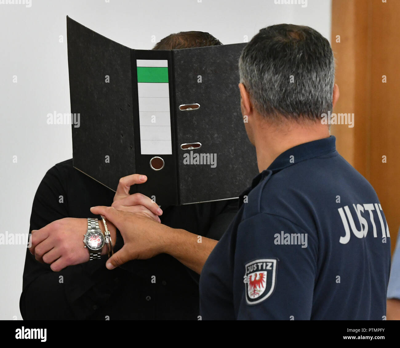 Potsdam, Brandenburg. 10th Oct, 2018. Covered by a file, a defendant enters the courtroom of the regional court. He had appealed against the amount of the total penalty in the trial for the arson attack on a gymnasium in Nauen. Credit: Bernd Settnik/dpa-Zentralbild/dpa/Alamy Live News - Stock Image