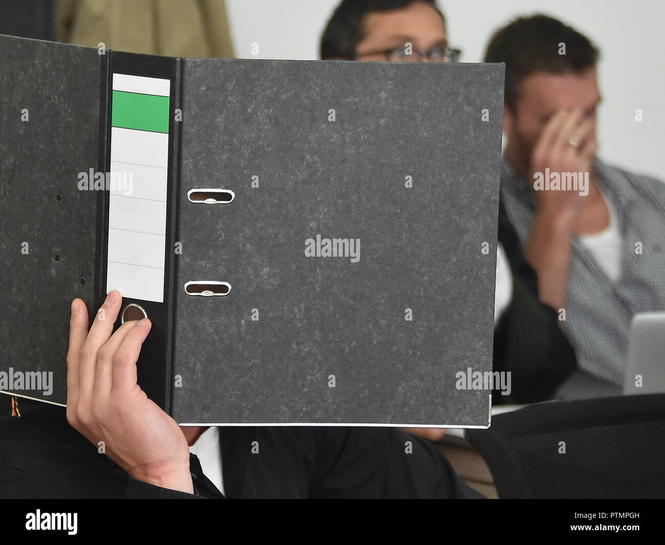 Potsdam, Brandenburg. 10th Oct, 2018. Covered by a file, a defendant sits in the courtroom of the regional court. He had appealed against the amount of the total penalty in the trial for the arson attack on a gymnasium in Nauen. On the right, the accused former NPD politician Maik Schneider, who was sentenced to nine and a half years in prison in the first trial for the attack, 2nd from right: his lawyer Oliver Milke. This first verdict was overturned by the Federal Supreme Court because of the bias of a juror. Credit: Bernd Settnik/dpa-Zentralbild/dpa/Alamy Live News - Stock Image