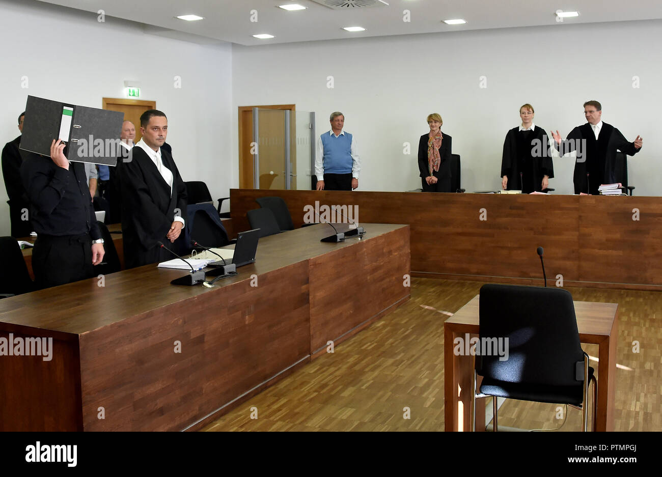 Potsdam, Brandenburg. 10th Oct, 2018. Klaus W. Feldmann (r), presiding judge at the Regional Court, opens the appeal of two defendants against an arson attack on a gymnasium in Nauen, which was to serve as refugee accommodation. One of the defendants (l) had lodged an appeal against the amount of the total fine and held a file in front of his face at the beginning of the trial. Credit: Bernd Settnik/dpa-Zentralbild/dpa/Alamy Live News - Stock Image