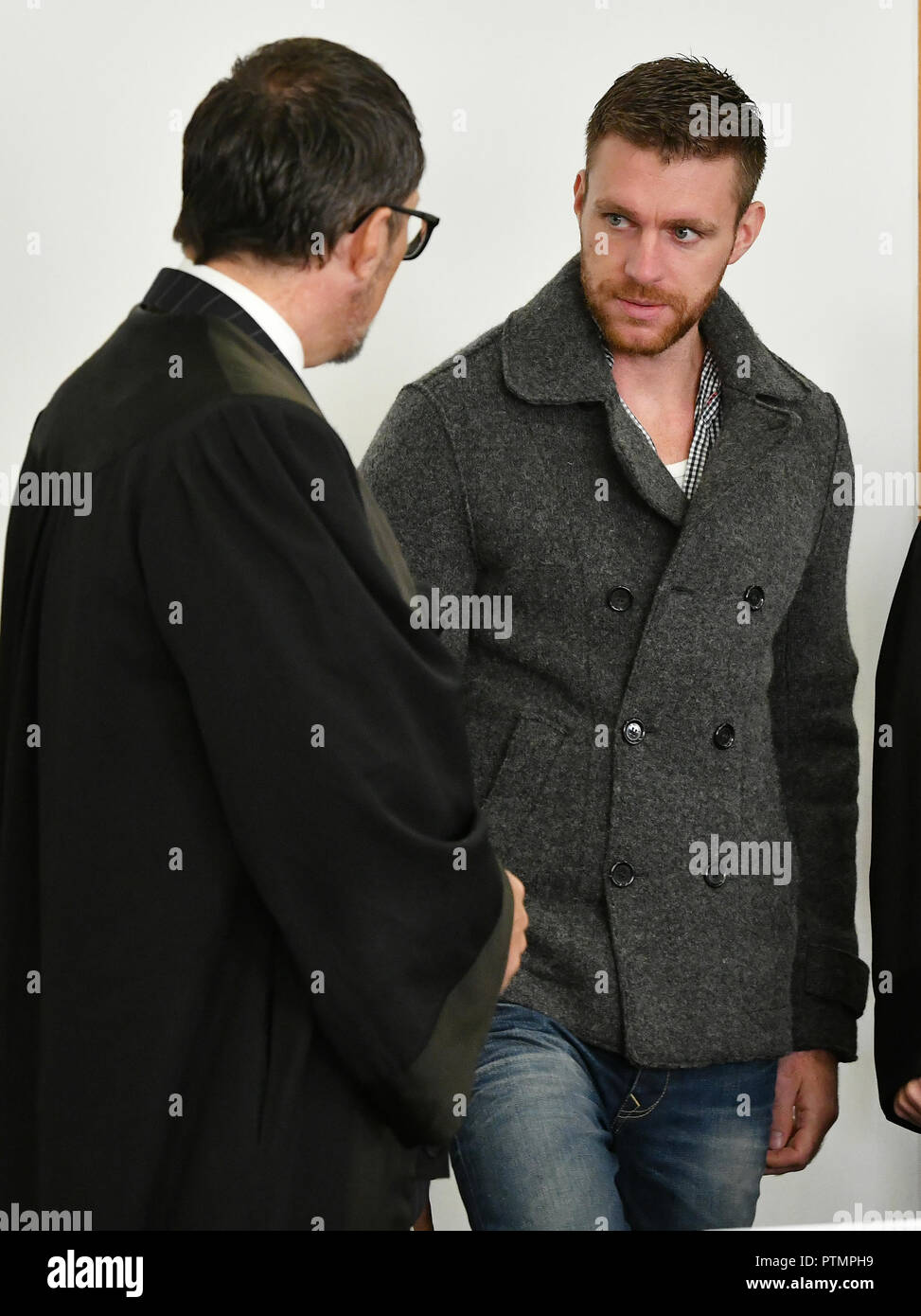 Potsdam, Brandenburg. 10th Oct, 2018. The accused former NPD politician Maik Schneider (r) is talking to his lawyer Oliver Milke in the regional court. He was sentenced to nine and a half years in prison in an initial trial for an arson attack on a gymnasium in Nauen that was to serve as a refugee shelter. This first verdict was overturned by the Federal Supreme Court because of the bias of a juror. Credit: Bernd Settnik/dpa-Zentralbild/dpa/Alamy Live News - Stock Image