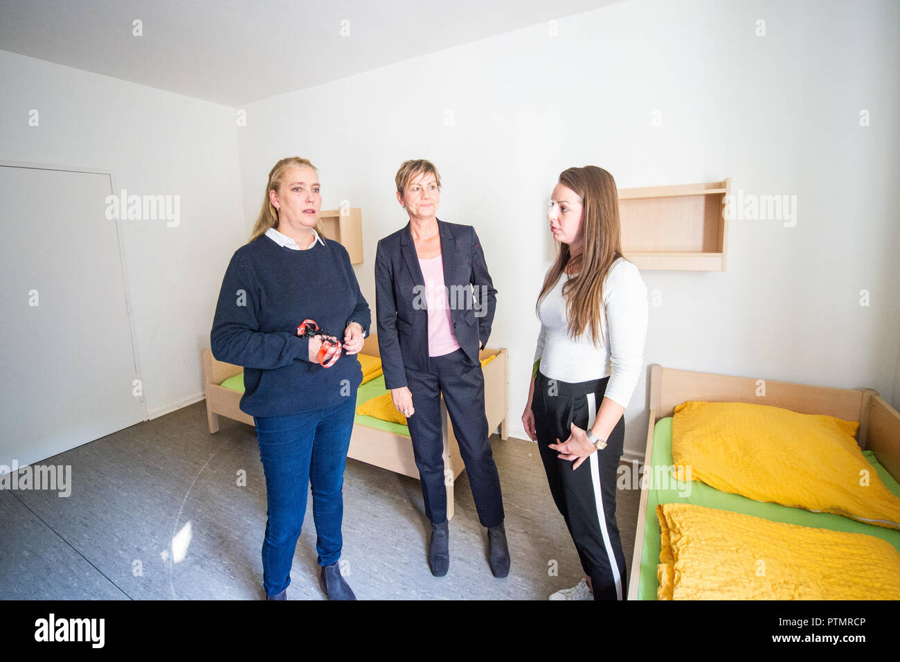 10 October 2018, Berlin: Viola Schröder (l-r), director of the emergency shelter for homeless families, Elke Breitenbach (Die Linke), senator for integration, labour and social affairs and Merle Mangels, social worker and deputy director of accommodation, stand in a room of the emergency shelter for homeless families. On Wednesday, the Berlin Senator for Integration, Labour and Social Affairs Breitenbach (Die Linke) visited Berlin institutions of homeless help. Photo: Arne Immanuel Bänsch/dpa - Stock Image