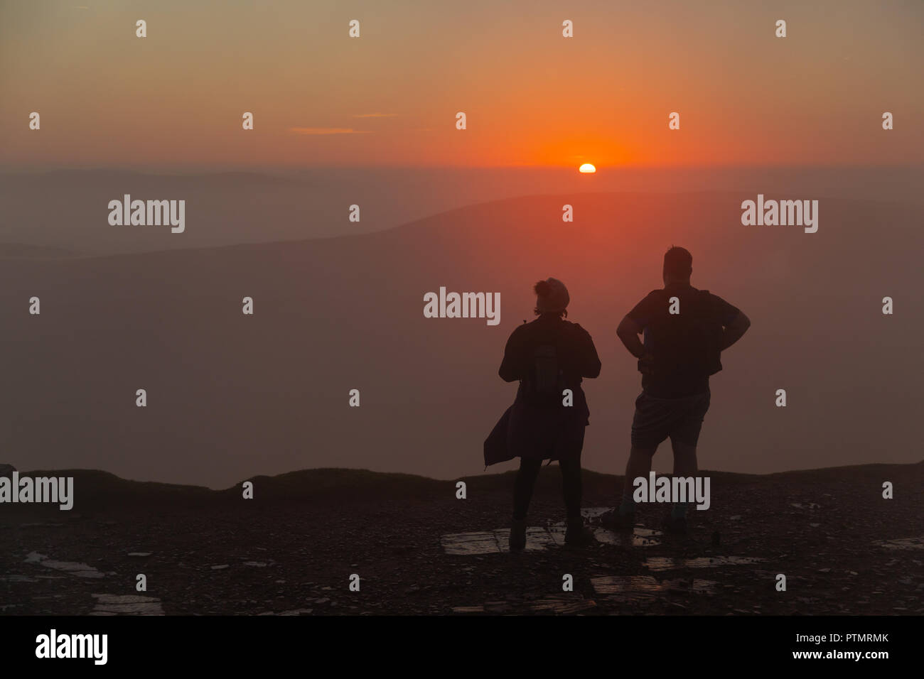 Pen y Fan, Brecon Beacons, Wales, UK. 10th October 2018. Hill walkers enjoy a dramatic sunrise from the peak of Pen y Fan, the highest mountain in southern Britain located in the Brecon Beacons.  On what is forecasted to be a warm and bright autumnal day with temperatures in south Wales predicted to peak over 21degrees celsius. Credit: Haydn Denman/Alamy Live News - Stock Image