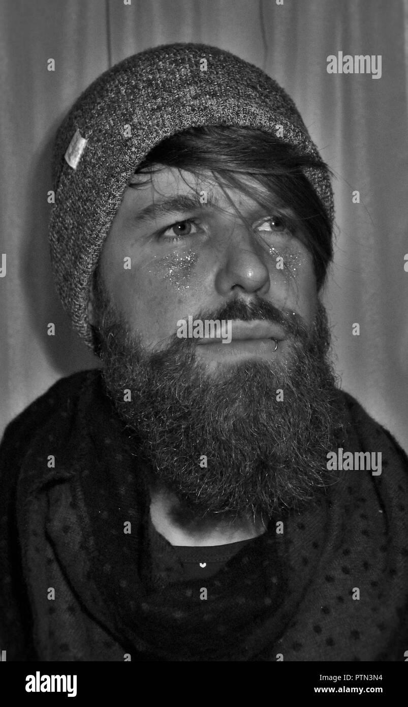 Bearded man, looking away. Beard, surf, piercing, smile. - Stock Image
