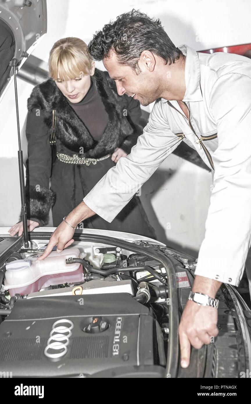 Autowerkstatt Mechaniker Kundin Kundendienst, Beratung erklaeren Wartung Werkstatt Mann Frau Kundenbetreuung Arbeiter Auto Fahrzeug Beruf Arbeit arbei Stock Photo