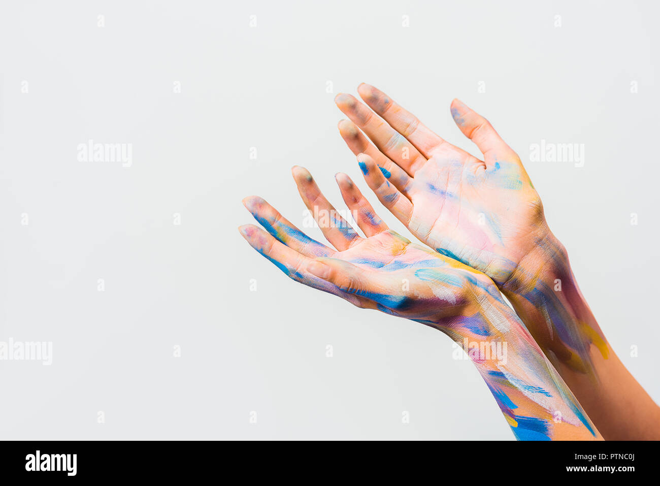 cropped image of girl with colorful bright body art showing hands isolated on white - Stock Image