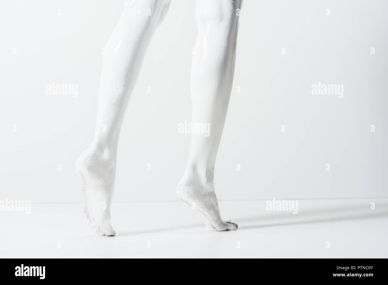 cropped image of girl with legs painted with white paint walking on white floor - Stock Image