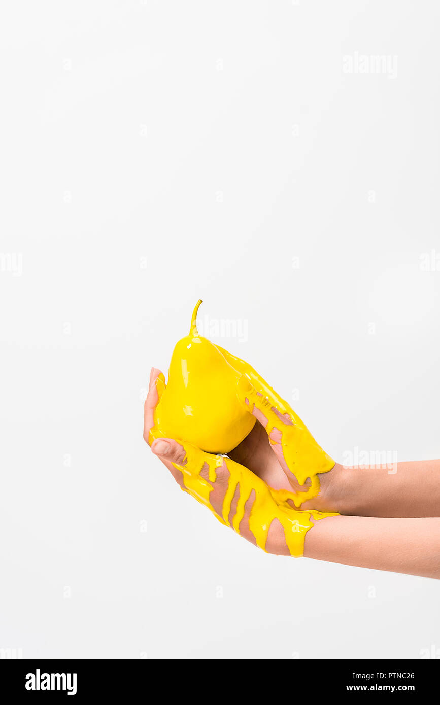 cropped image of woman in yellow paint holding pear in hands isolated on white - Stock Image