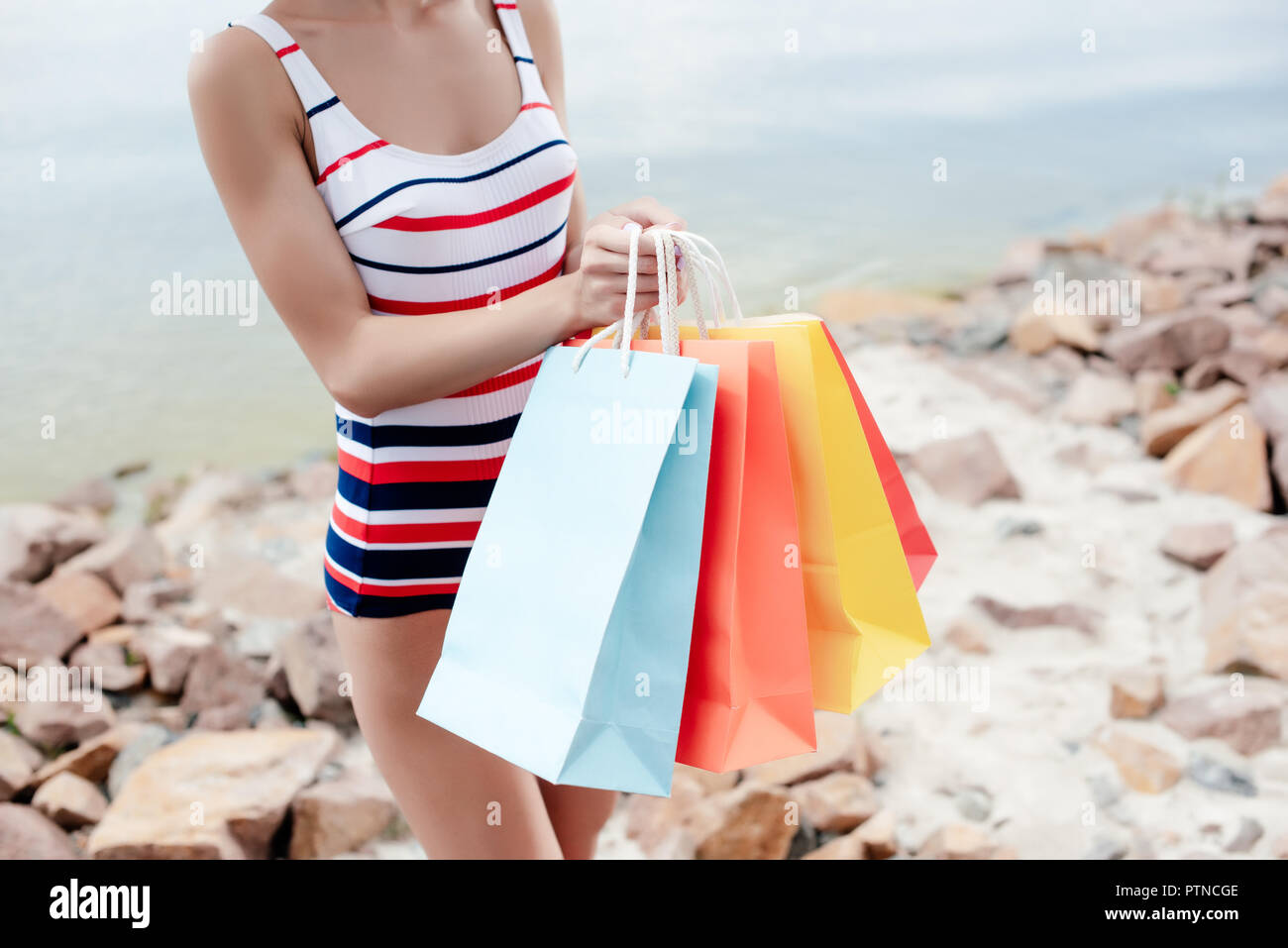 8bf56fac88 partial view of girl in retro striped swimwear holding colorful shopping  bags on shore - Stock