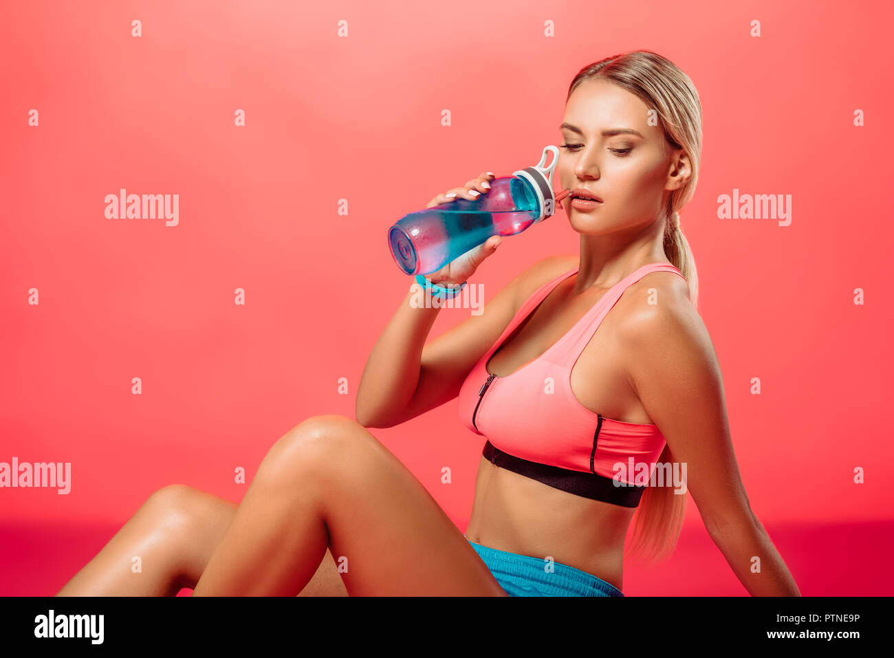 attractive sportswoman drinking water from sport bottle on red Stock Photo