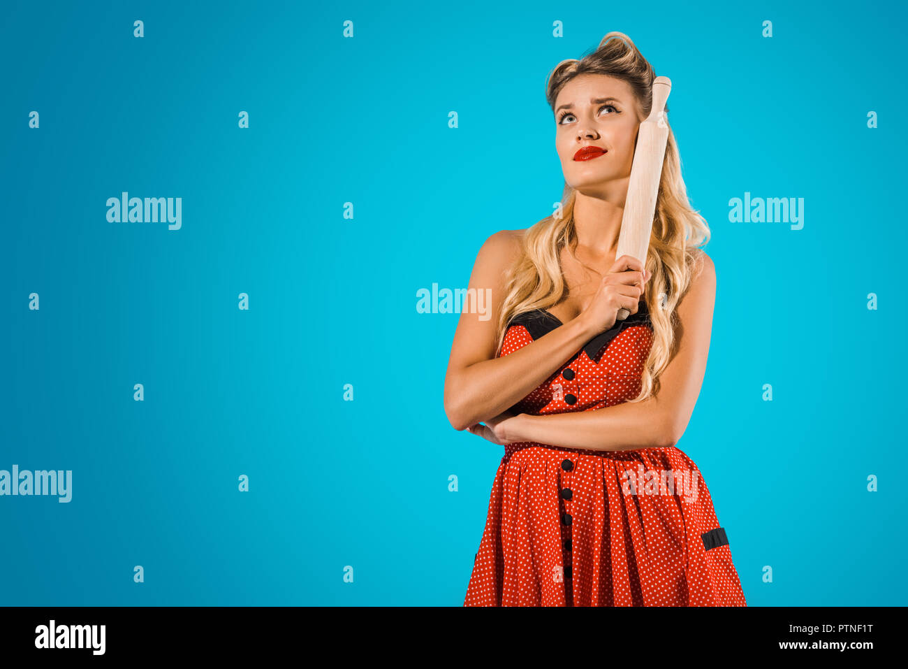 29f1b2325649 portrait of attractive pensive woman in pin up style dress with rolling pin  looking away on