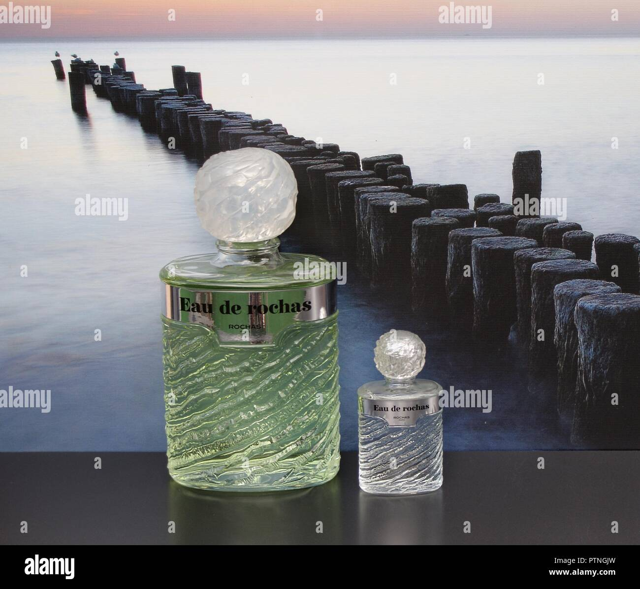 Eau de Rochas, fragrance for ladies, large perfume bottle next to a commercial perfume bottle in front of the picture of a groyne in the sea - Stock Image