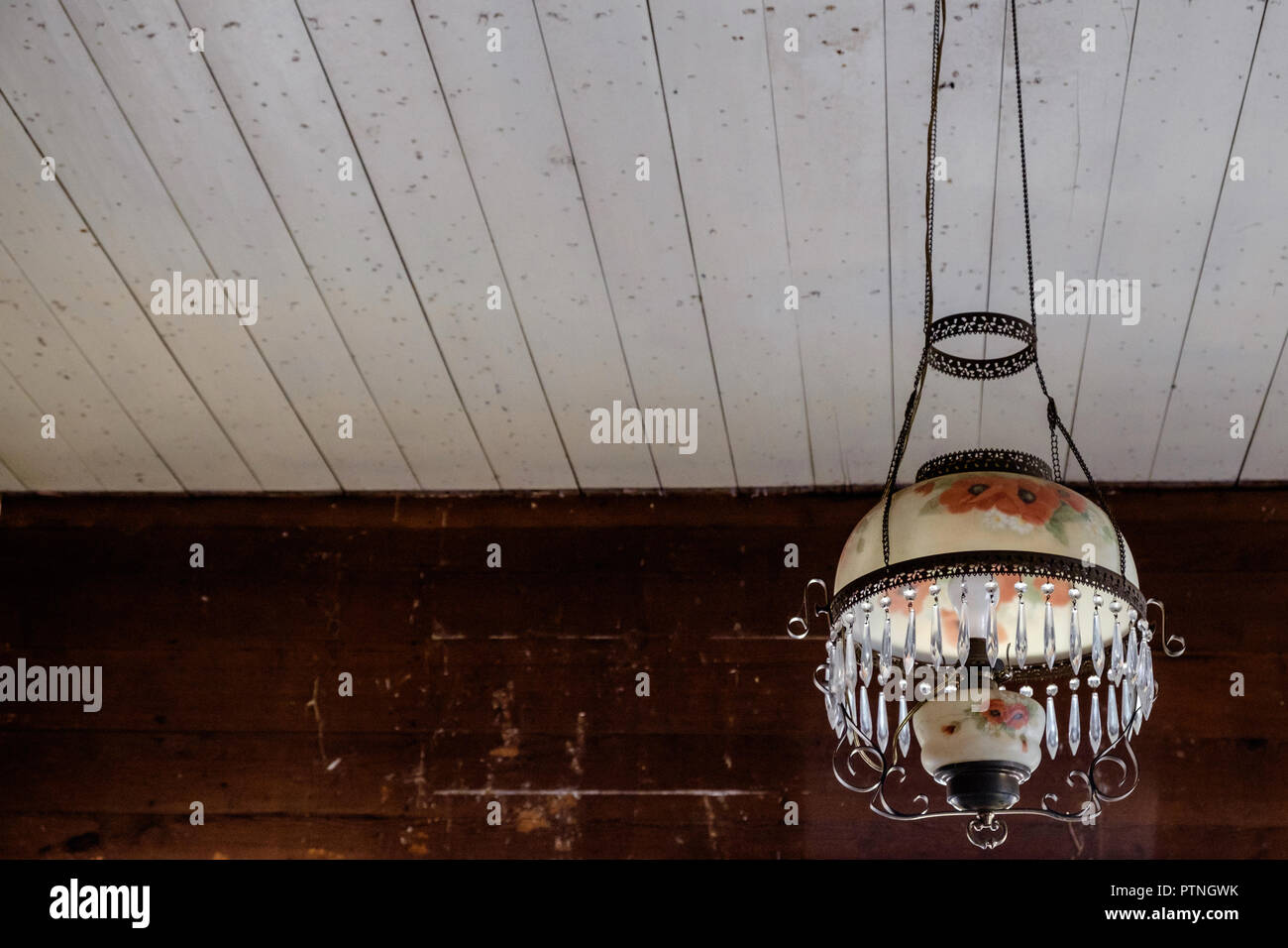 Victorian style, glass hanging parlour lamp, with painted flowers on shade, prisms &  brass trim. Chestnut Square Historic Village, McKinney,Texas. - Stock Image