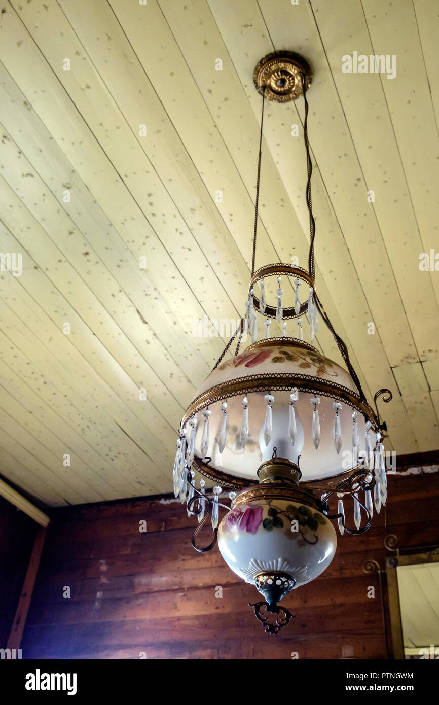 Victorian style, glass hanging parlour lamp, with painted flowers on shades, prisms & brass trim. Chestnut Square Historic Village, McKinney,Texas. - Stock Image