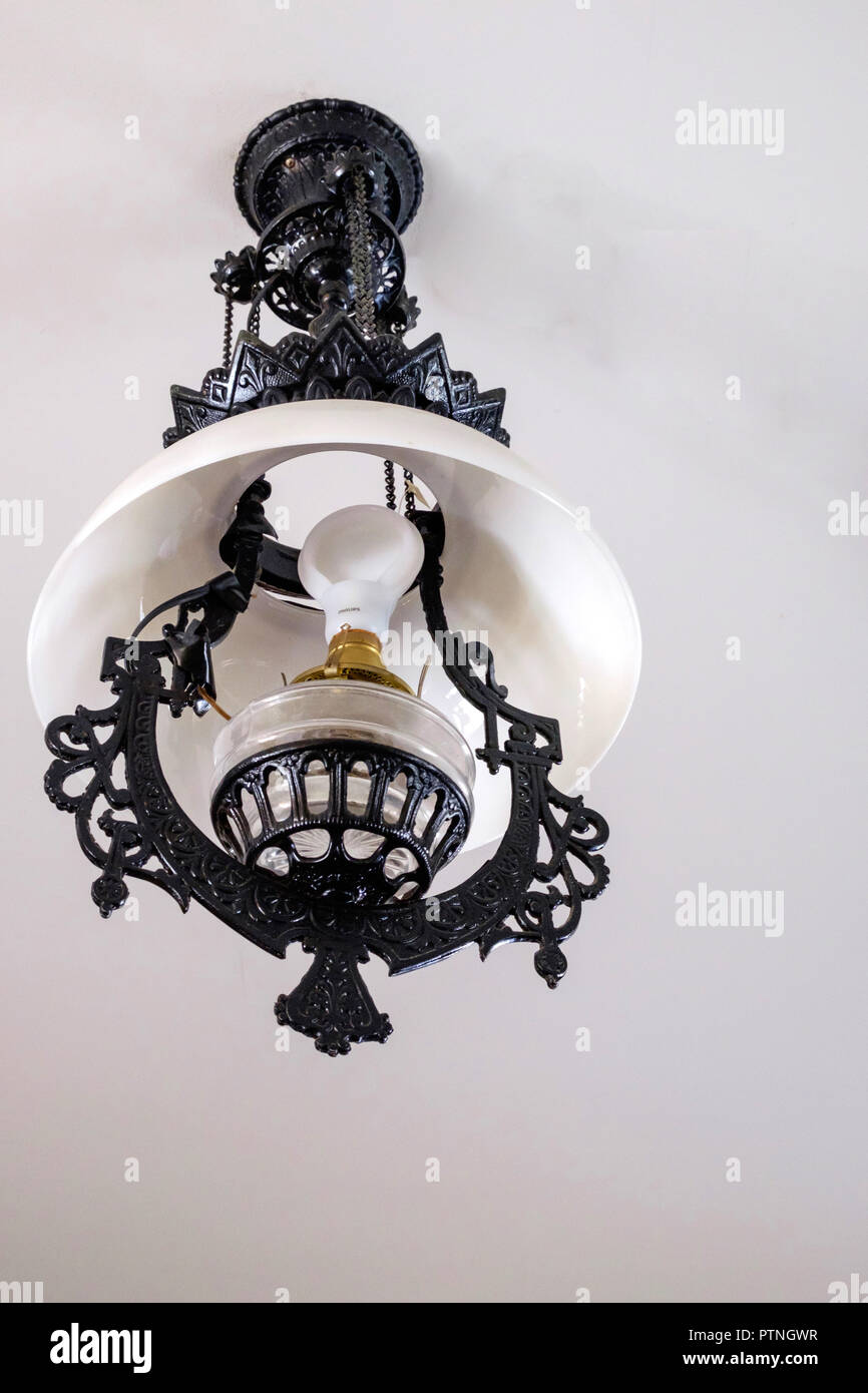Rustic style, white glass hanging parlour lamp, with black wrought iron trim. copy space, portrait. Chestnut Square Historic Village, McKinney,Texas. - Stock Image