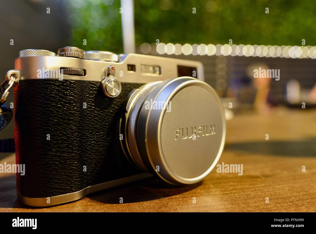 Fujifilm x100f camera on a table at night - Stock Image