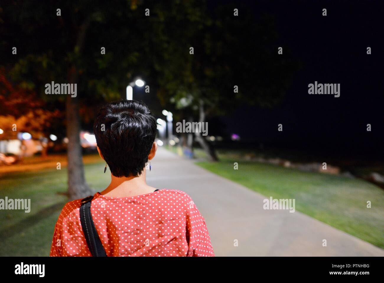 A woman walks alone down a path at night, Townsville, Queensland, Australia Stock Photo