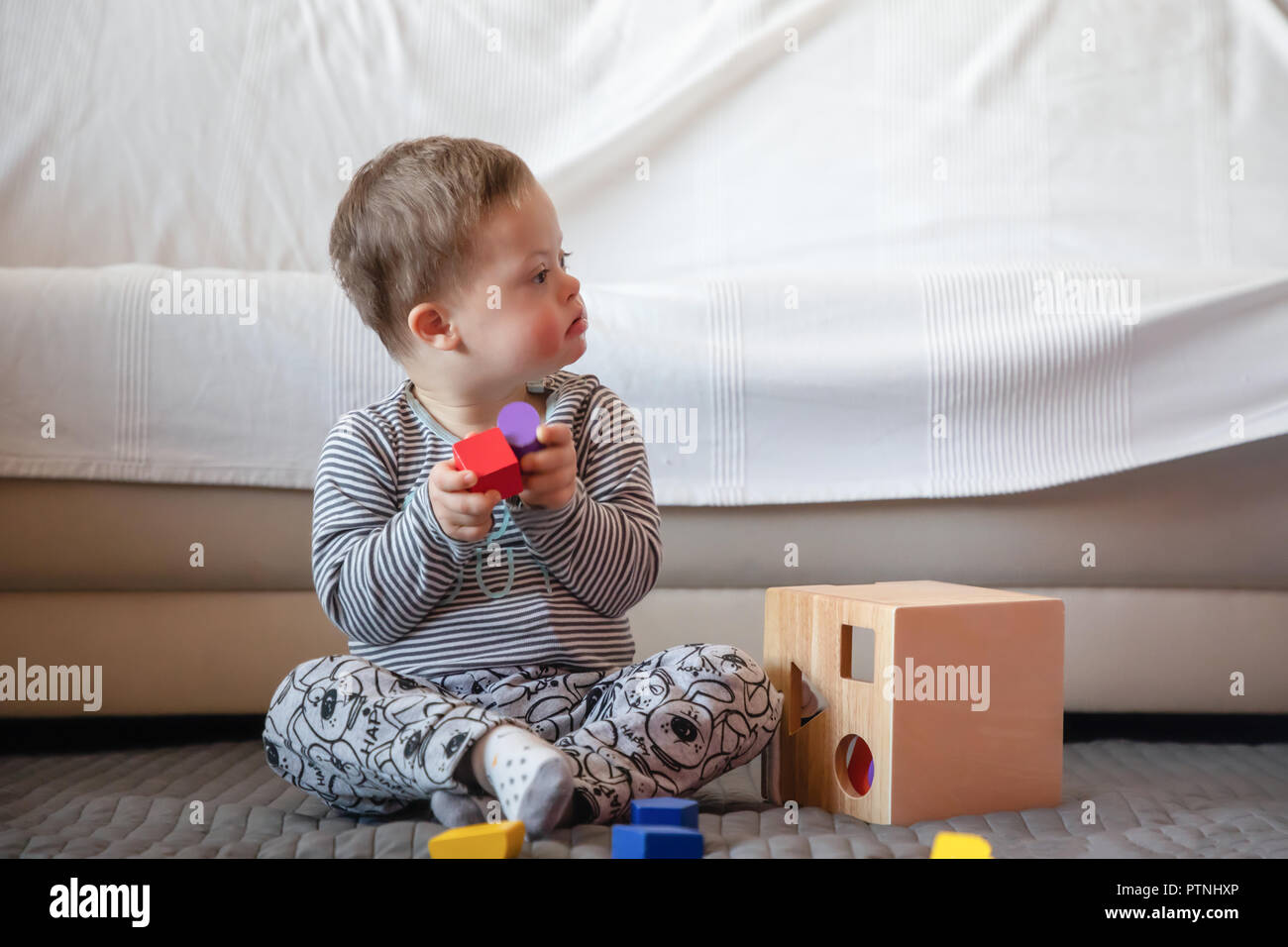 Portrait of cute boy with Down syndrome playing in home - Stock Image