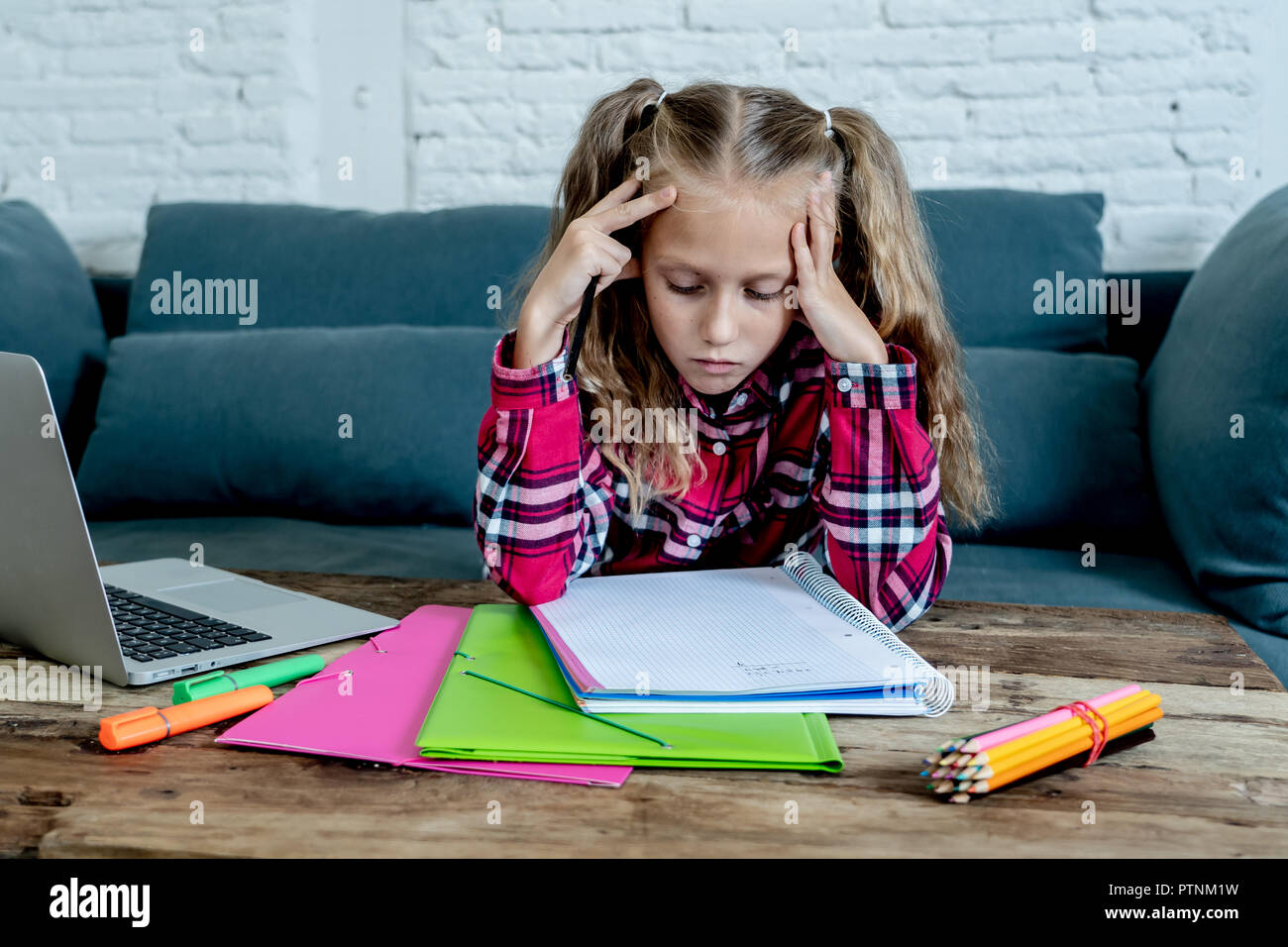Beautiful cute blonde 9 years elementary student feeling sad bored and a overwhelmed trying to study at home in learning difficulties exams homework a - Stock Image