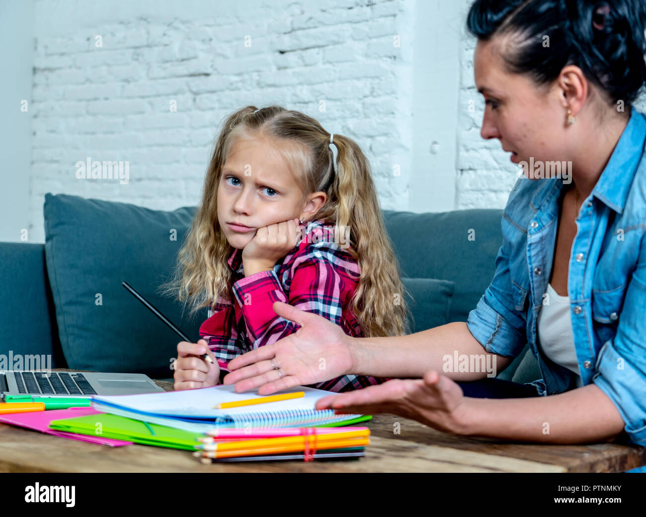 Mother Becoming Frustrated With Daughter Whilst Doing Homework Sitting On Sofa At Home - Stock Image