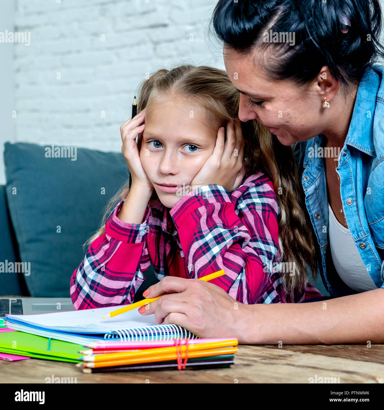 Sweet mum with daughter unable to concentrate whilst doing homework sitting on sofa at home in learning difficulties homework parenting and education  - Stock Image