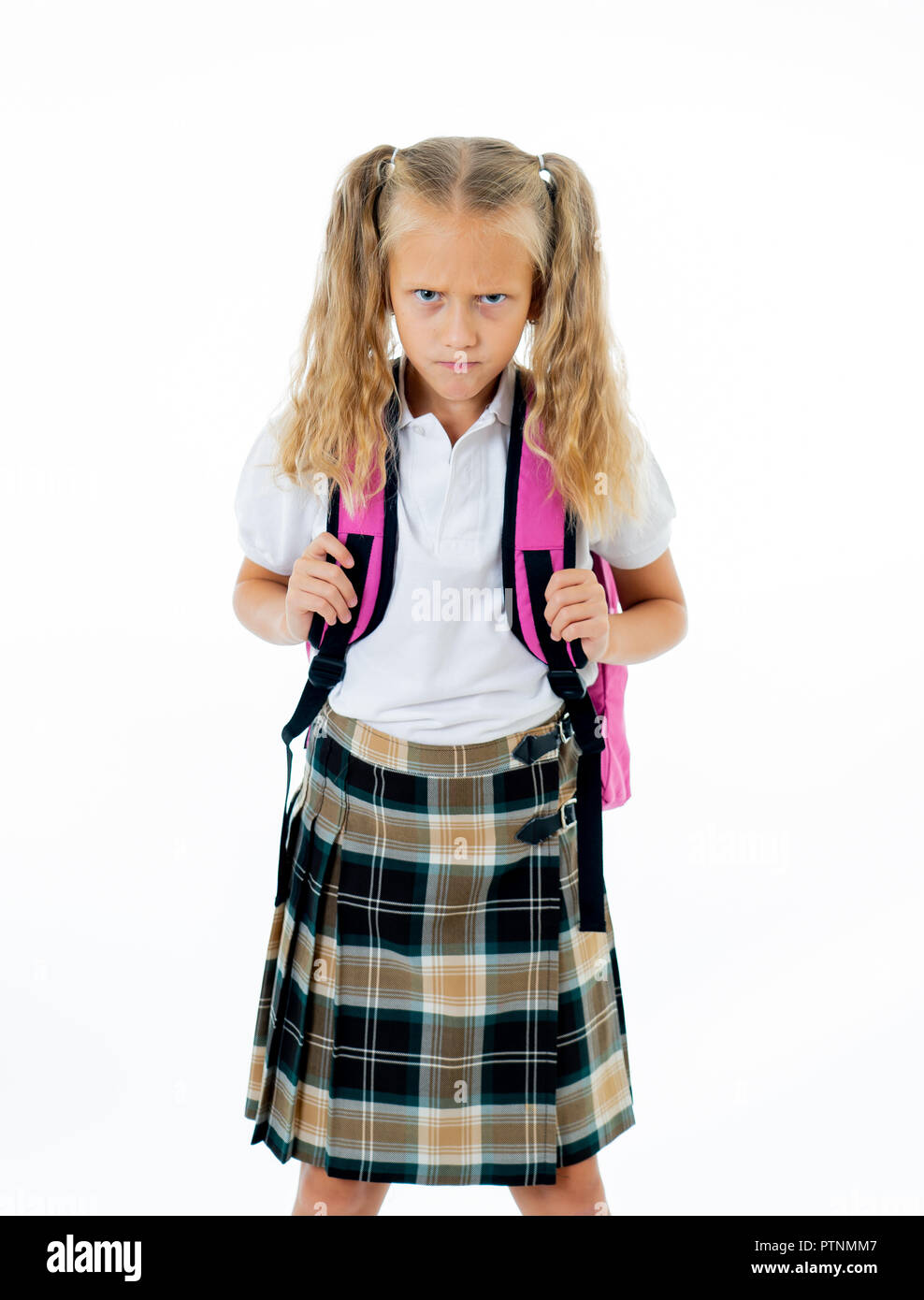 Sweet beautiful little girl in school uniform feeling angry and frustrated looking at the camera isolated on white background in homework learning dif - Stock Image