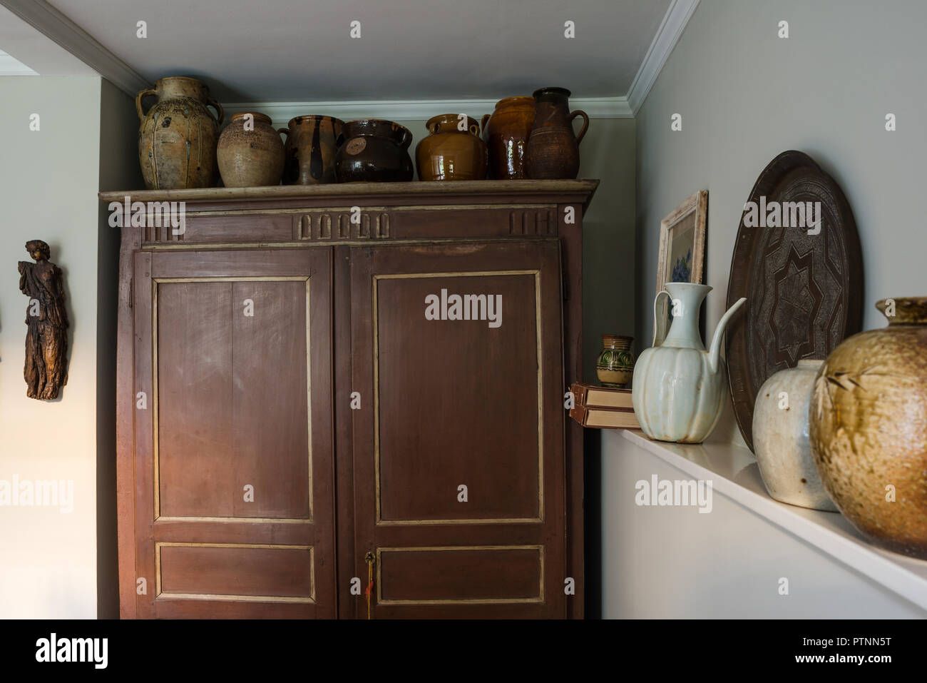 French salt-glazed cruches jugs are arranged along the top of the rustic French painted armoire - Stock Image
