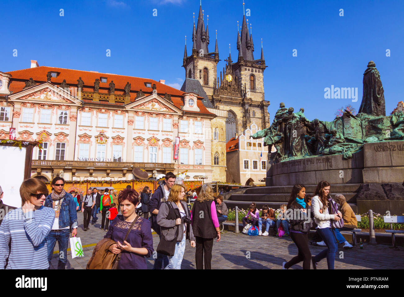 Prague, Czech Republic : Tourists at the Old Town Square stand by the Jan Hus Memorial designed by Ladislav Šaloun in 1915 with the Church of Our Lady - Stock Image