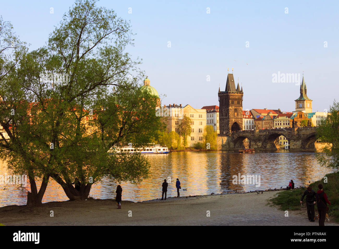 Prague, Czech Republic : Tourists walk at sunset by the shore of the Vltava river by the Charles Bridge. - Stock Image