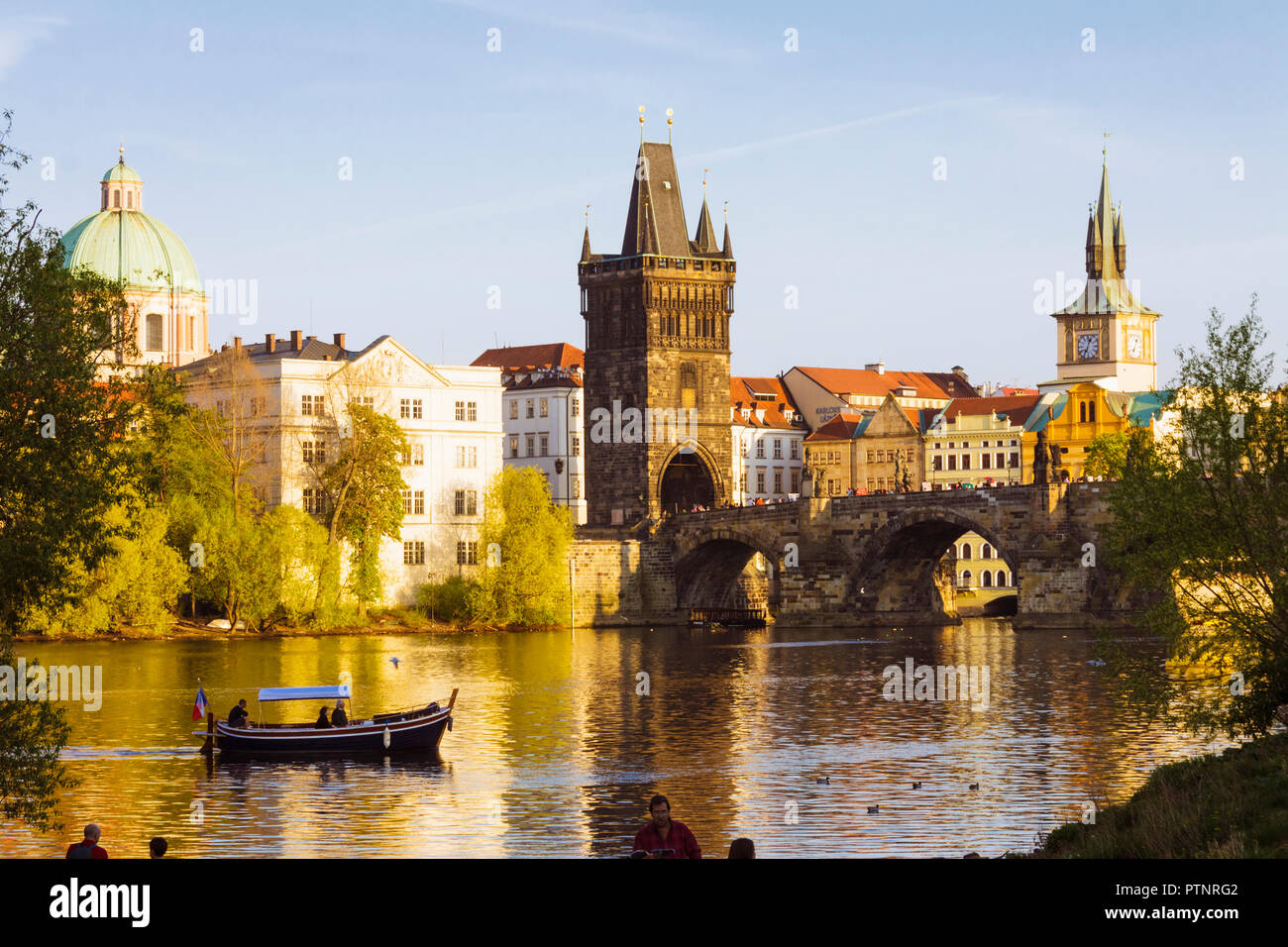 Prague, Czech Republic : A sightseeing boat full of tourists sails towards Charles Bridge at sunset. - Stock Image