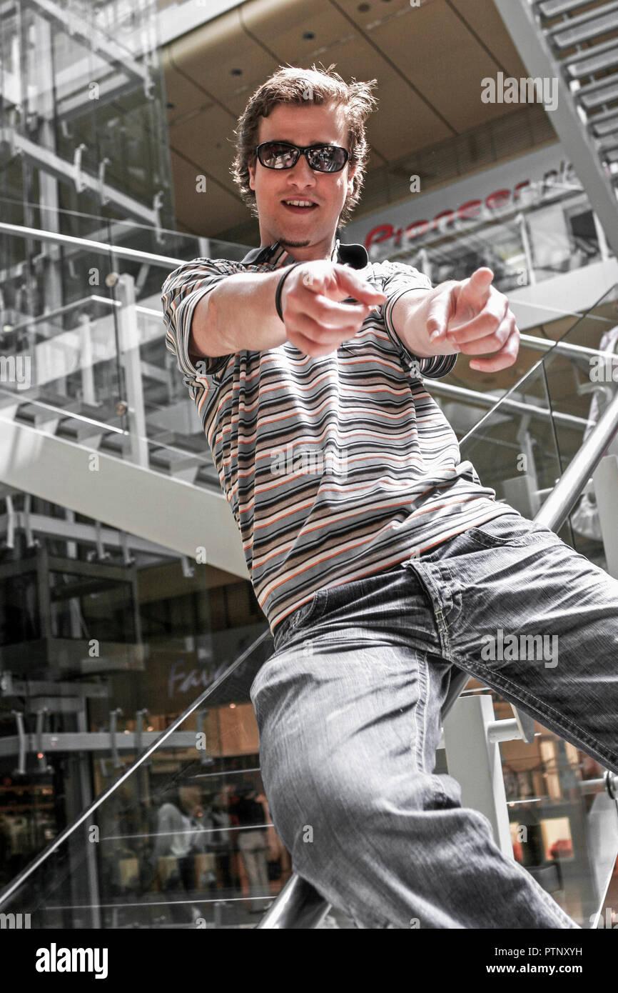Mann Jung Laecheln Blick Kamera Portrait Bart Sonnenbrille Rutschen Gelaender Gestik Natuerlichkeit Natuerlich Menschen Generationen Teenager Lifestyl - Stock Image