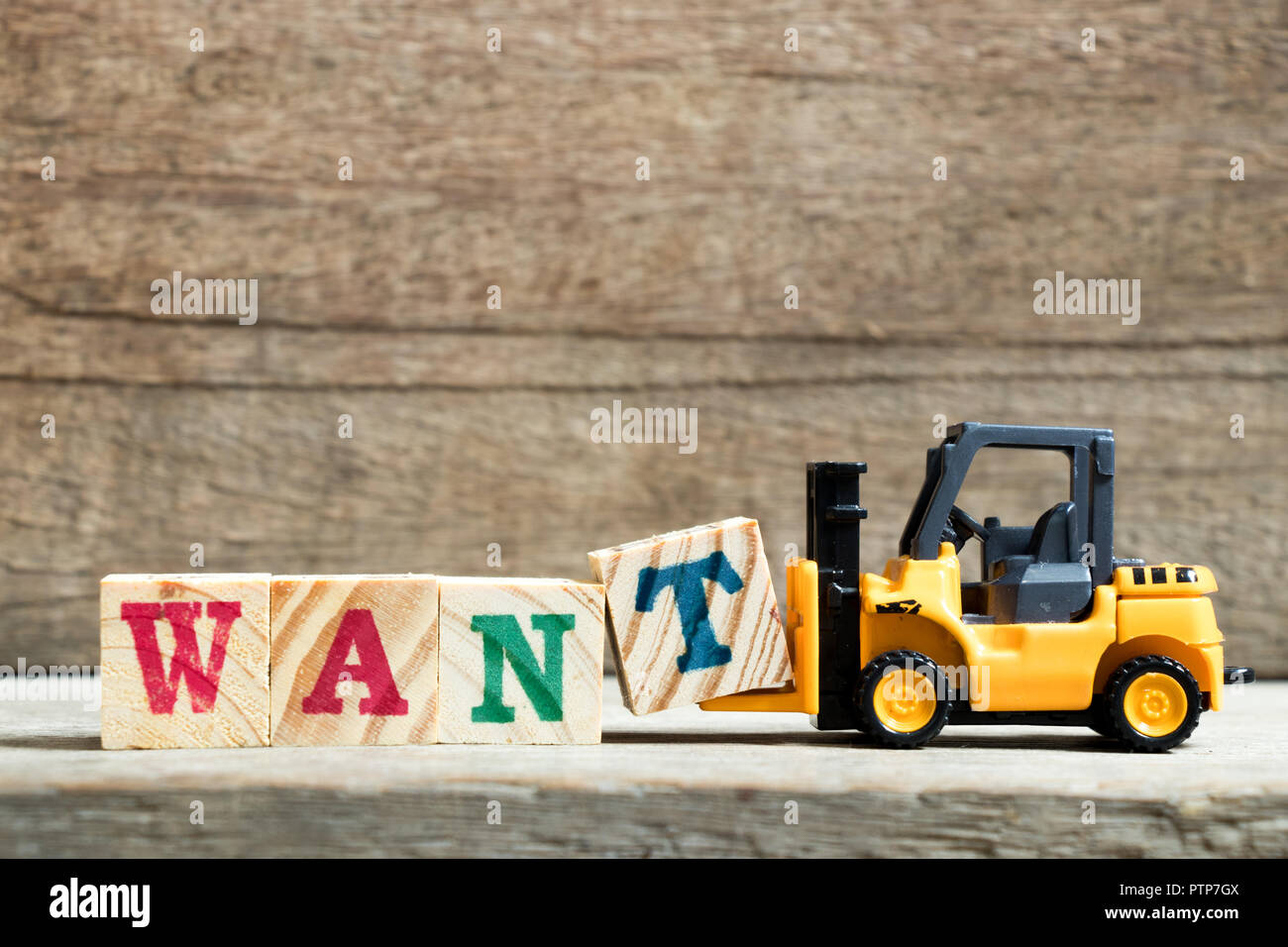 Yellow toy forklift hold letter block t to complete word want on wood background - Stock Image