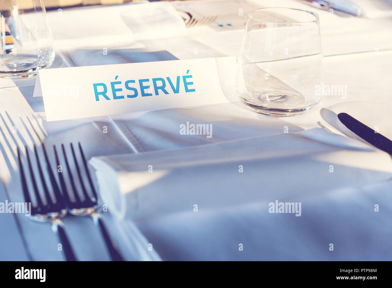 Reserved Table. A tag of reservation placed on the wood table. Reserved logo. Reservation sign. Paper tag with reservation logo. Reserved table in a r - Stock Image