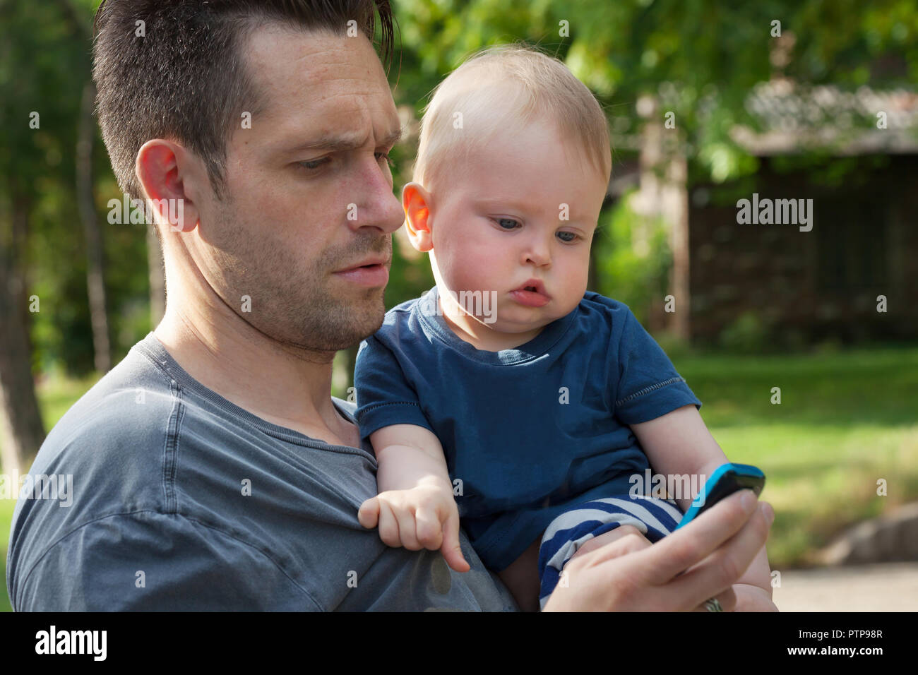 Father and son looking at a mobile phone having fun - single parent and 13 month old baby enjoying outdoors - Stock Image
