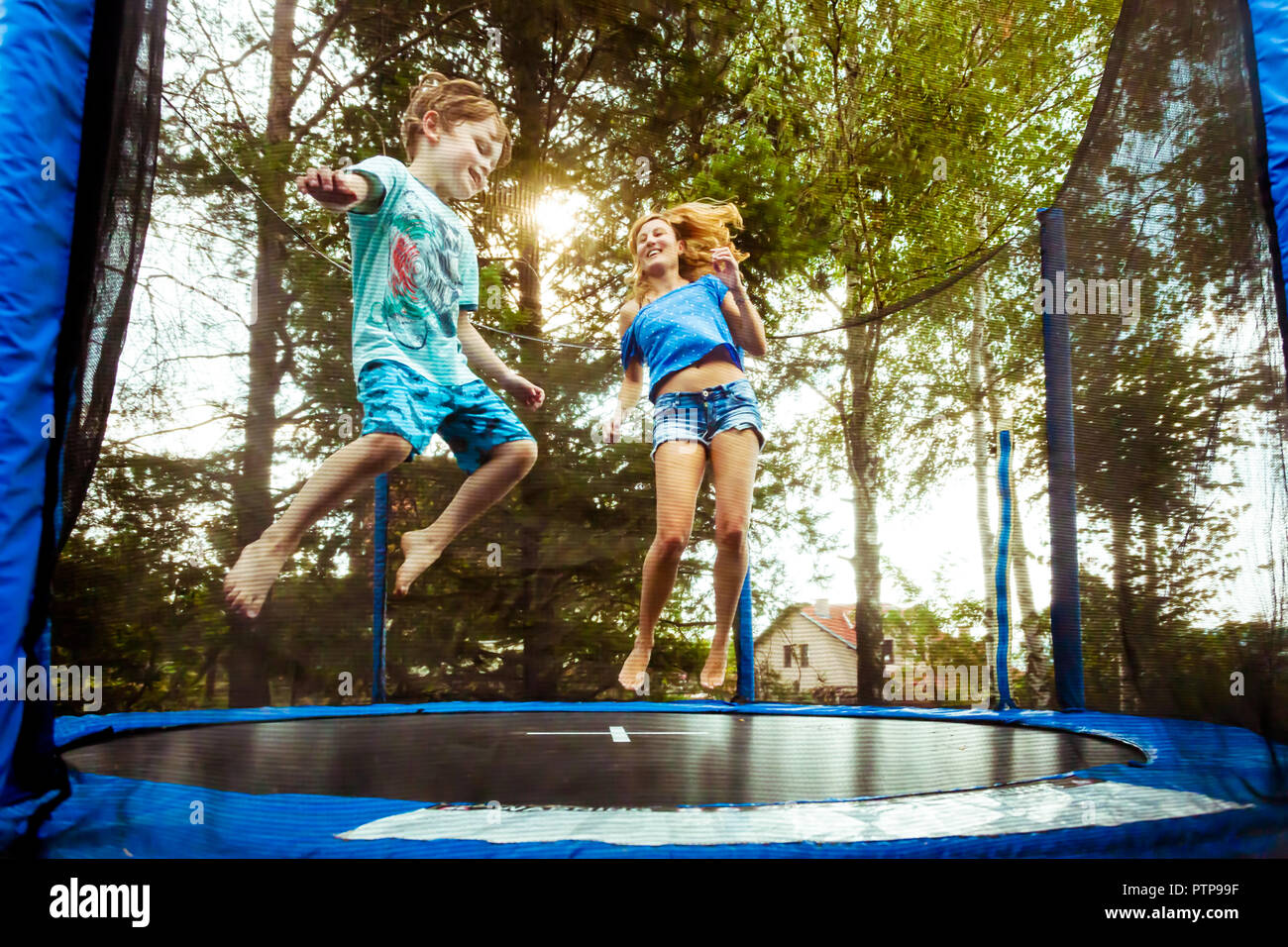 Single Parent Mother having fun with her son on the trampoline - Stock Image
