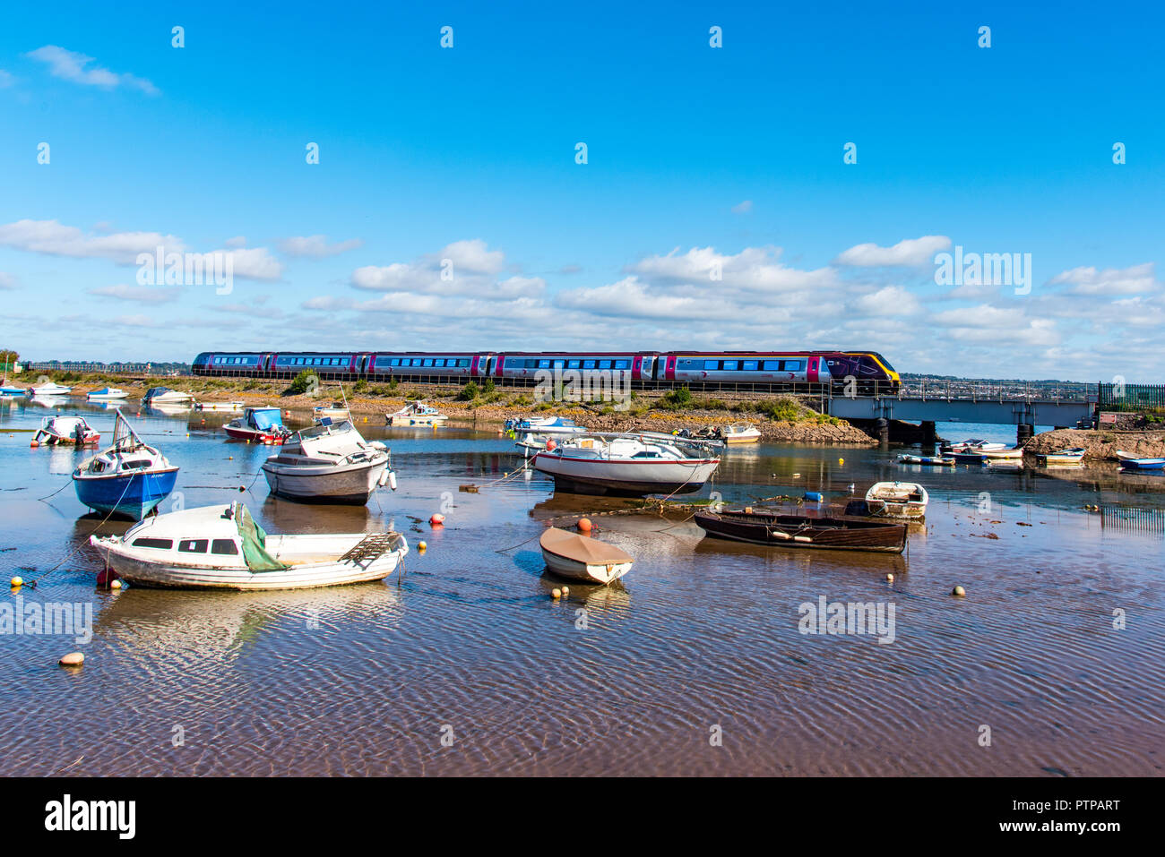 COCKWOOD, STARCROSS, DEVON, UK - 03OCT2018:  CrossCountry class 220 Voyager trainset passes the harbour at Cockwood on the Exe Estuary. - Stock Image