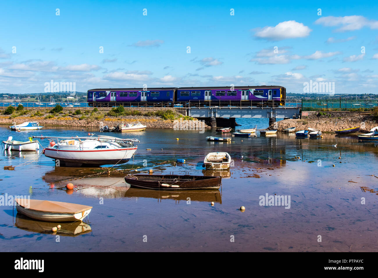 COCKWOOD, STARCROSS, DEVON, UK - 03OCT2018 First Great Western class 150 Sprinter train 150267 passes the harbour at Cockwood on the Exe Estuary. - Stock Image