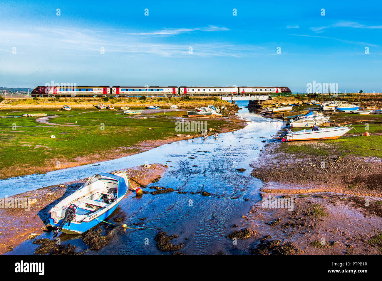 COCKWOOD, STARCROSS, DEVON, UK - CrossCountry class 220 Voyager trainset passes the harbour at Cockwood on the Exe Estuary. - Stock Image