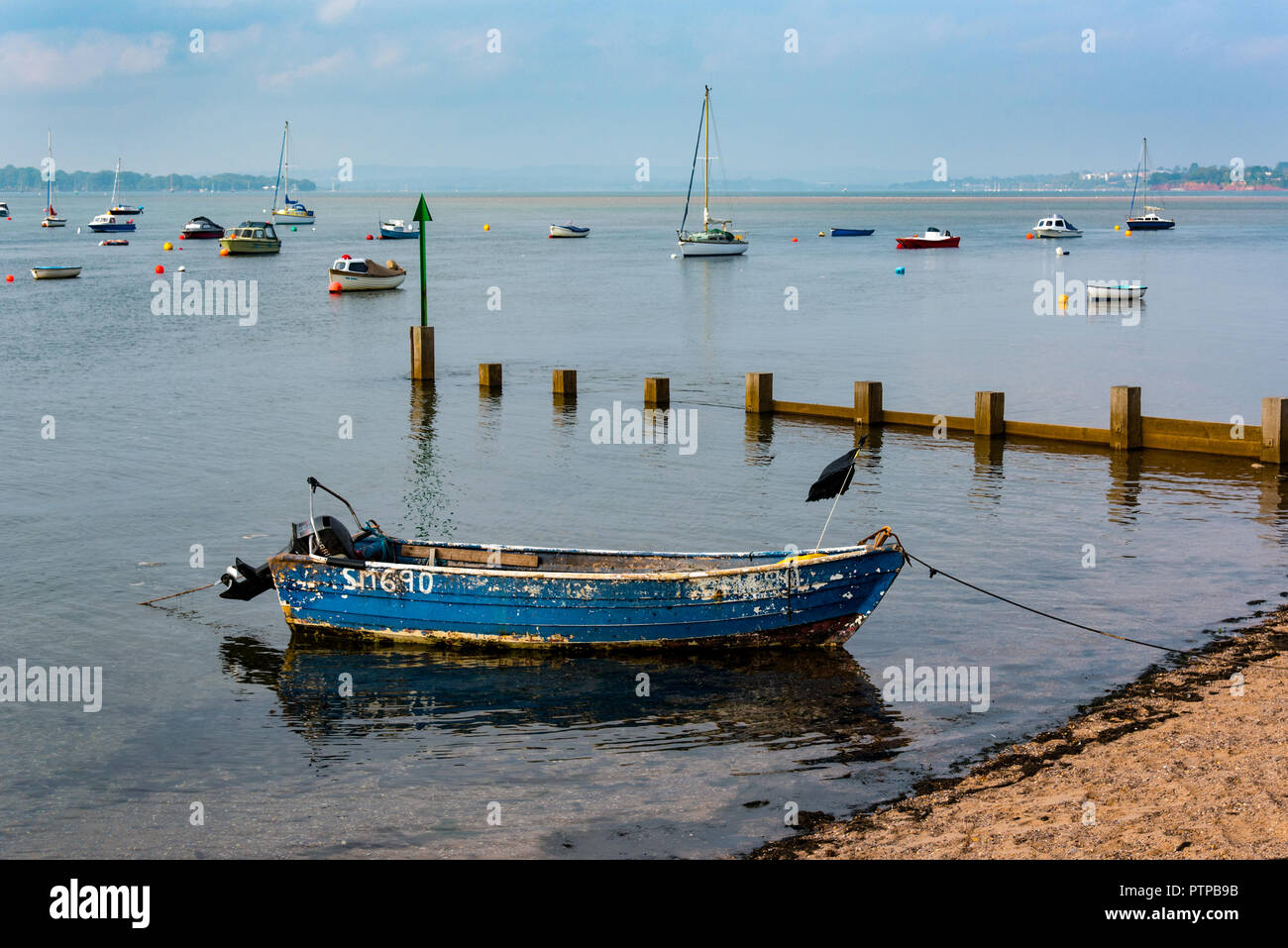 EXMOUTH, DEVON, UK - 05OCT2018:  Old boat  at Shelly Beach, with the Exe Estuary behind. - Stock Image