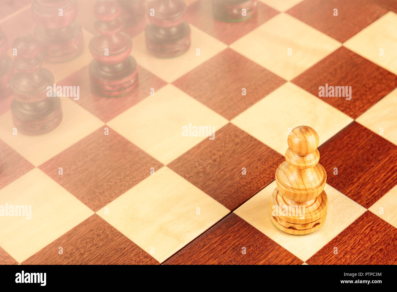 A pawn on a chessboard, a metaphor for the first step, with a background blurred for copy space - Stock Image