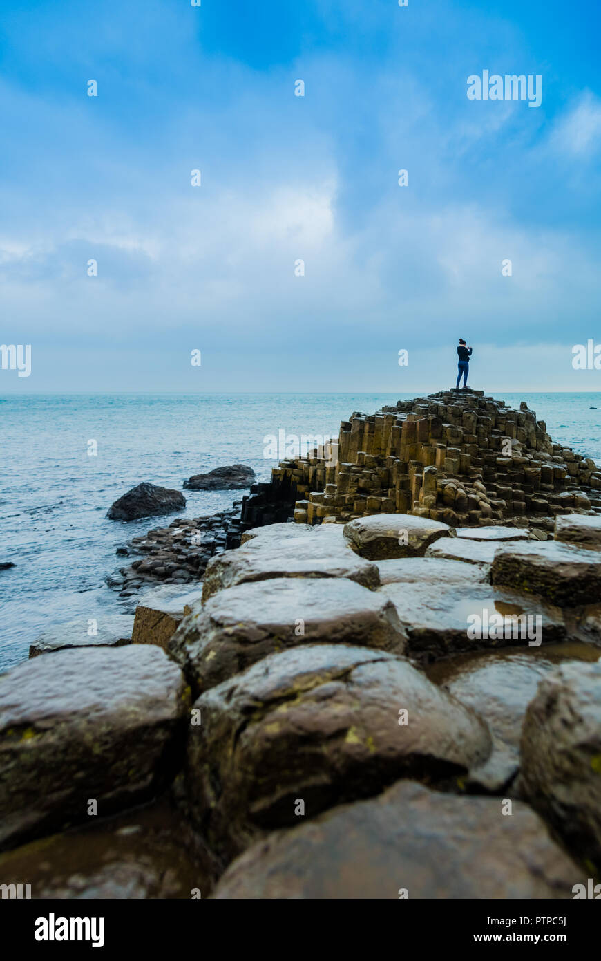 Tourists taking pictures on the famous Giants' Causeway stones in Northern ireland - Stock Image