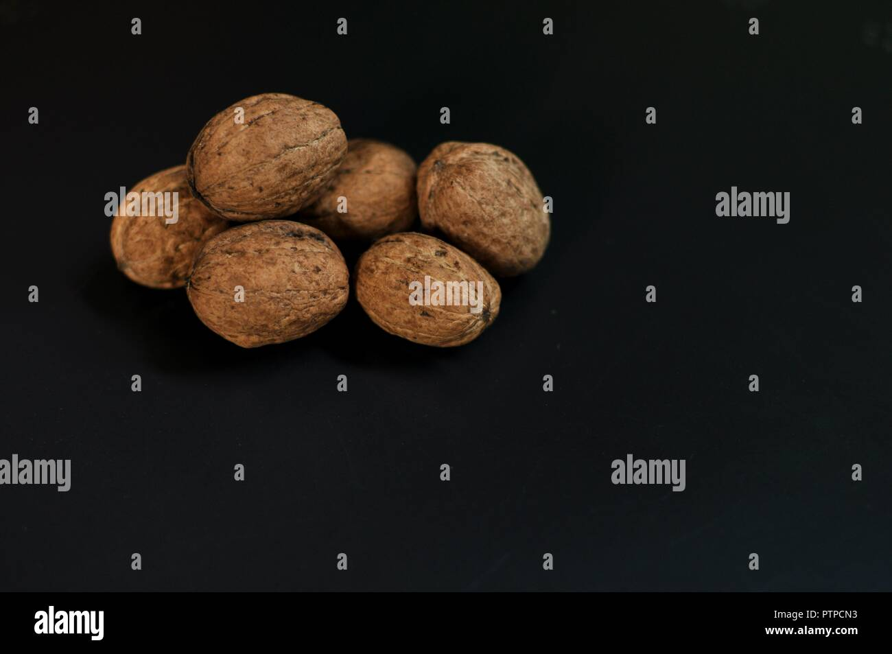 Heap (pile, stack) of nuts in shell isolated on black background with copy space. Underexposed, front side view - Stock Image