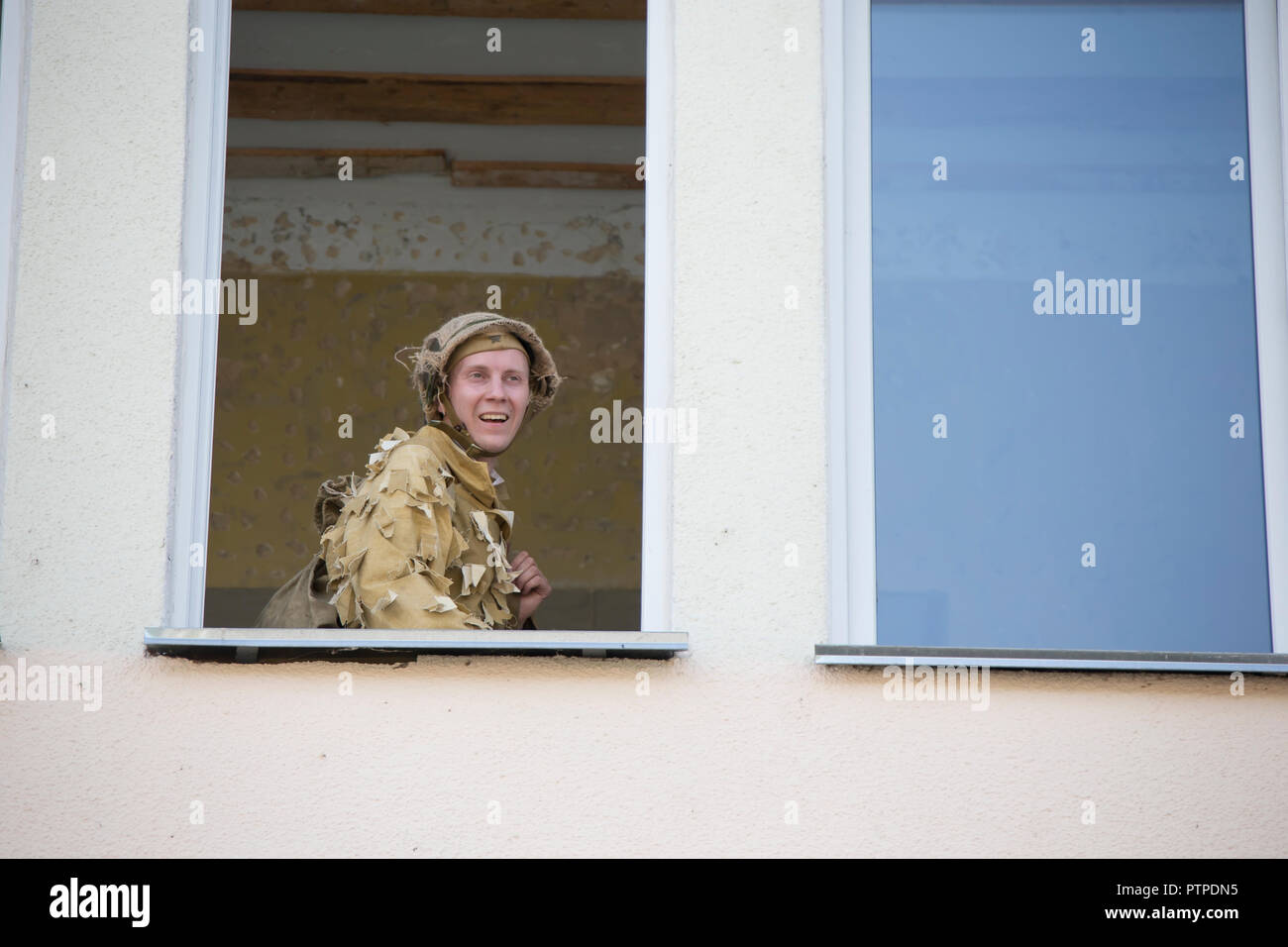 Belarus, Gomel. May 9, 2018. Victory Day. Reconstruction take Reichstag.Soldier in camouflage uniform in a helmet looks out the window - Stock Image