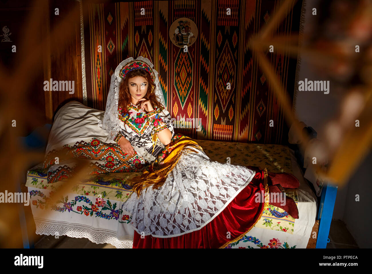 beautiful girl in a hut in national Slavic costume. - Stock Image