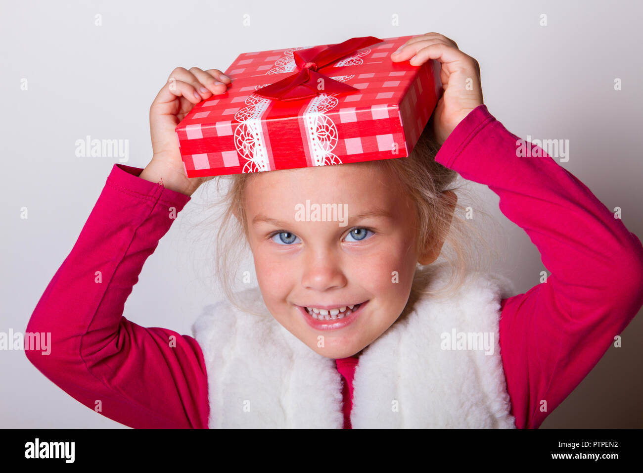 little girl in a red sweater and a fur vest clothed a lid from a gift box on her head as a hat. she laughs, rejoices, fools around, fun. New Year's co - Stock Image