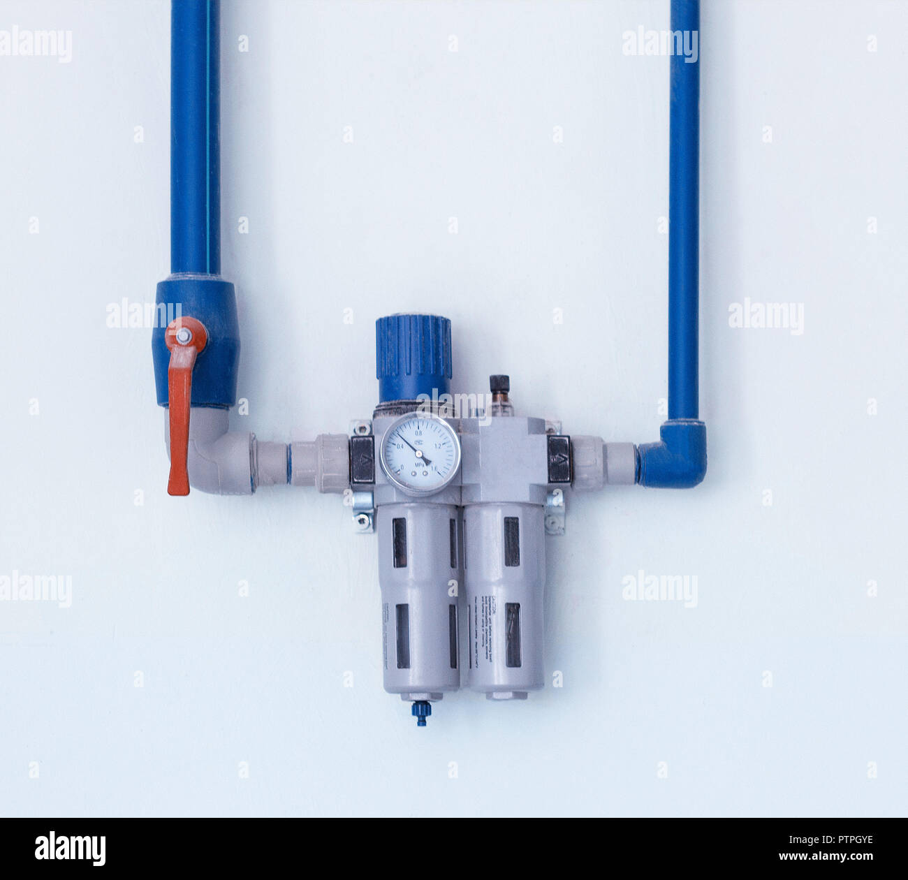 A modern filter with a water gauge for cleaning from debris and heavy metals, located on the wall, a water pipe, water purification - Stock Image