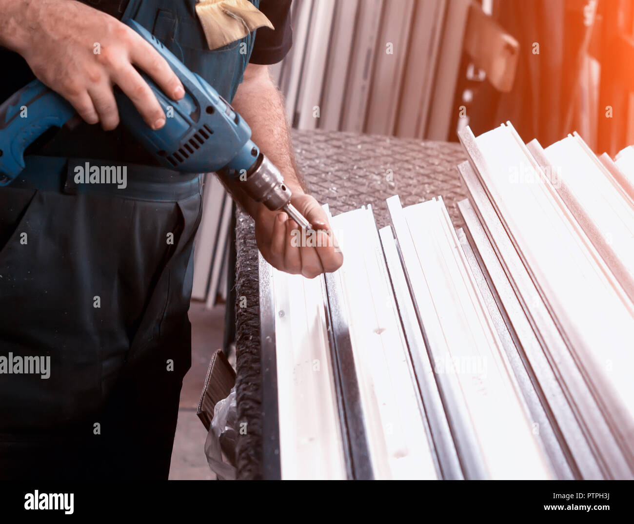 Production of pvc windows, the worker is screwed with a screwdriver with a snap to the pvc window, close-up, screwdriver - Stock Image