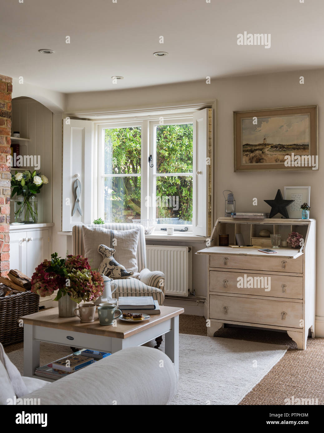 Upcycled antique bureau beside window in 18th century Norfolk cottage - Stock Image