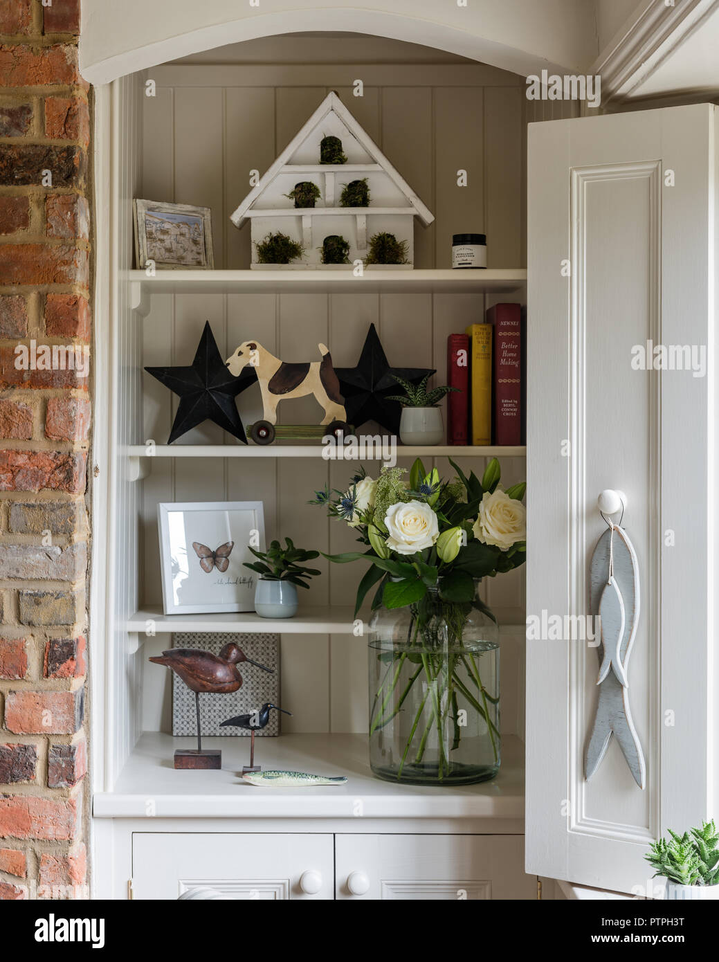 Books and ornaments with cut flowers on recessed shelving in 18th century Norfolk cottage - Stock Image