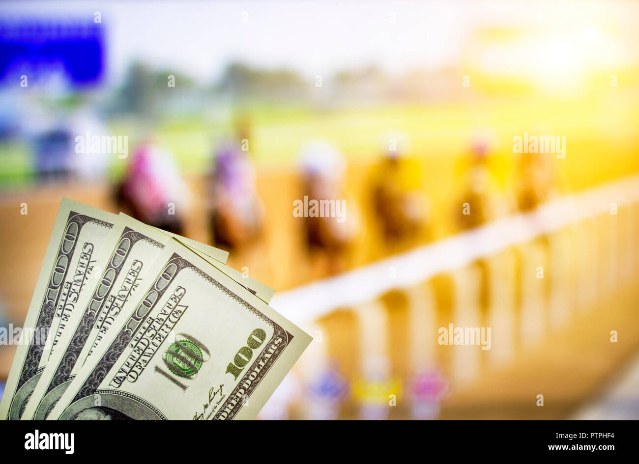 Money dollars on the background of a TV on which show jumps on horses, sports betting, dollars, races - Stock Image